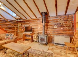 View of Aspen Hideout CAbin living room with TV and cozy wood stove