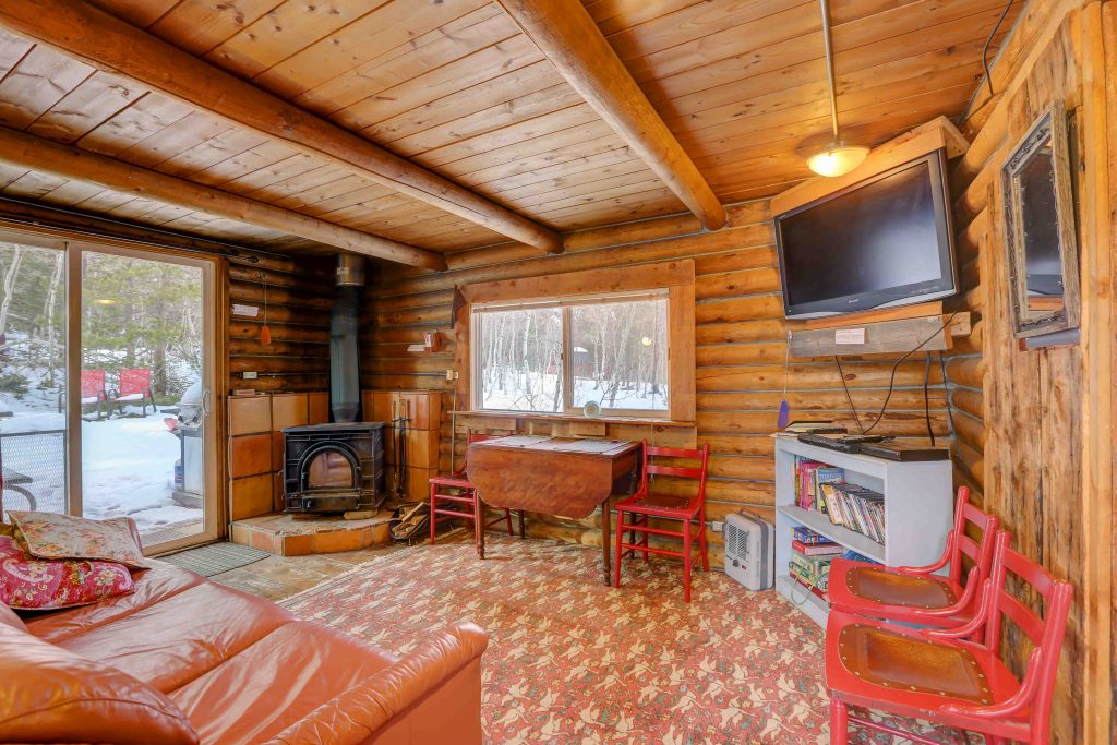 Cozy living room at Honeymoon Hideout, with TV, wood stove and couch