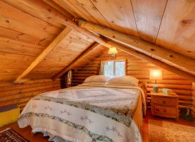 Cozy master bedroom with wooden log support beams and queen bed