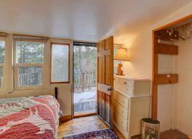 This second floor bedroom provides access to this vacation cabin's large deck with scenic views