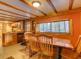 View of cabin's dining area, kitchen, and outdoor with propane grill